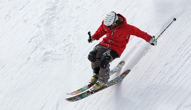Skier red jacket going down slope