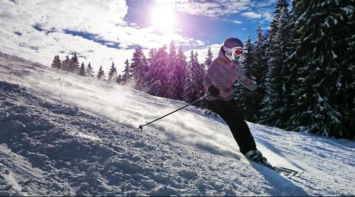 Skier wearing goggles and helmet on a slope blue sky