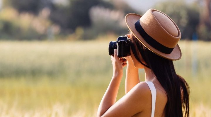 Woman in barley field taking photo